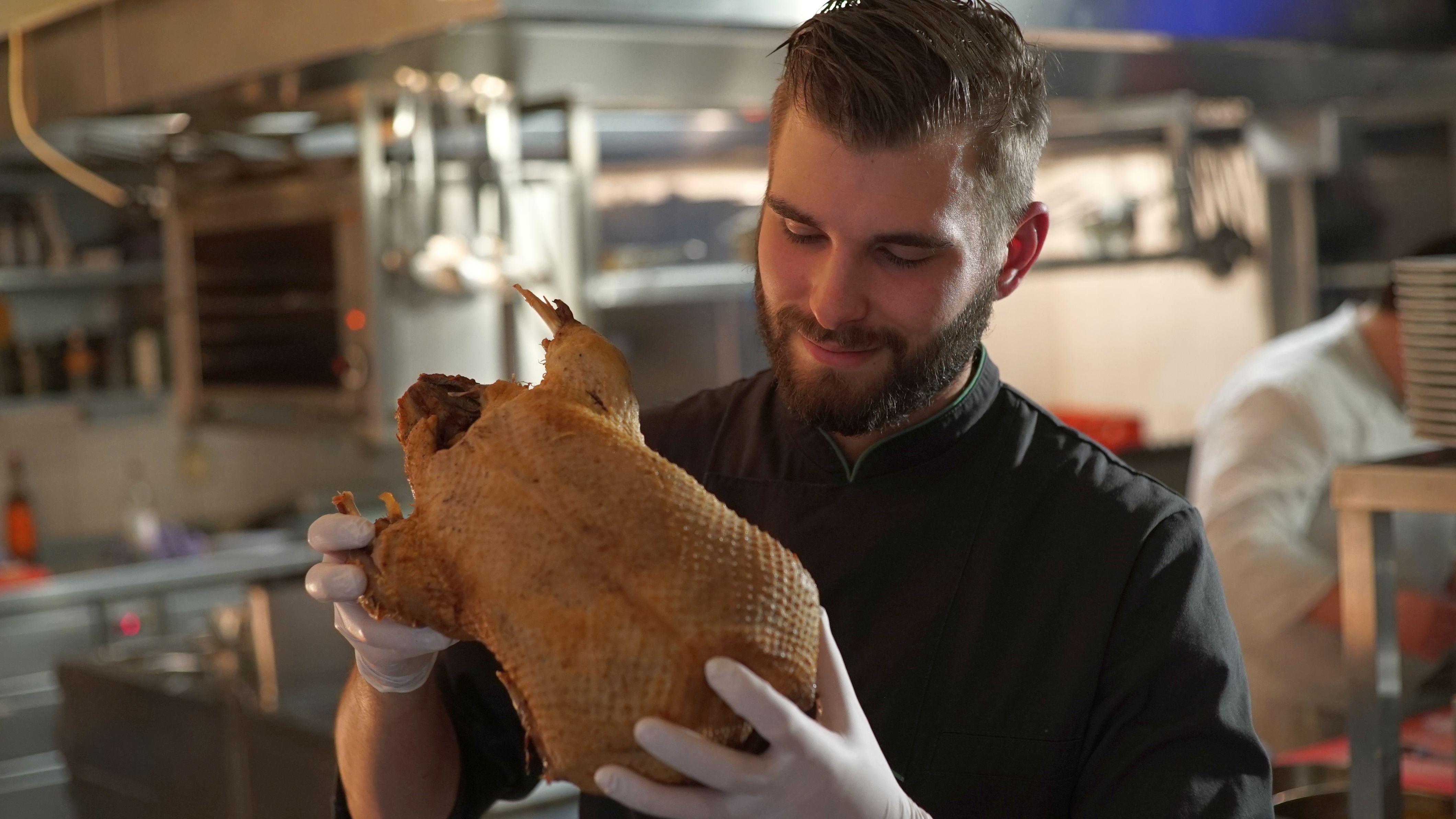 Ein Koch, der eine gerupfte Gans in den Händen hält.